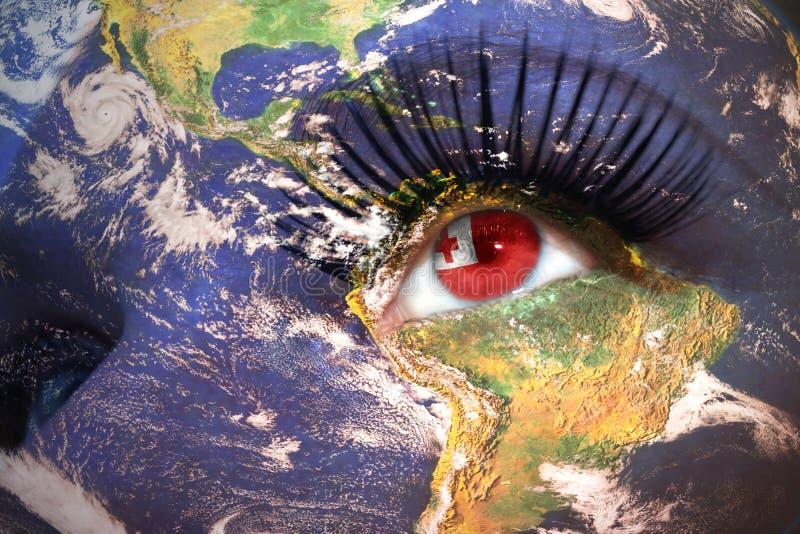 Сторона женщины с текстурой земли планеты и Тонга сигнализируют внутри глаза стоковая фотография