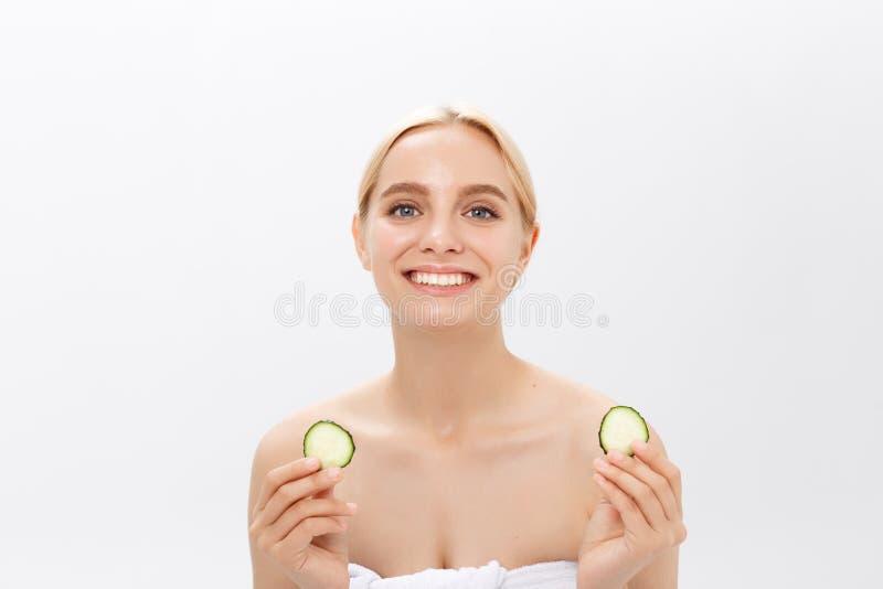 Сторона конца-вверх красивой женщины с чистой свежей здоровой кожей и с кусками огурца Изолировано на белизне стоковое фото