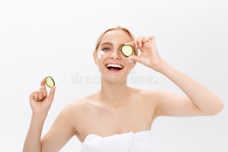 Сторона конца-вверх красивой женщины с чистой свежей здоровой кожей и с кусками огурца Изолировано на белизне стоковые фотографии rf