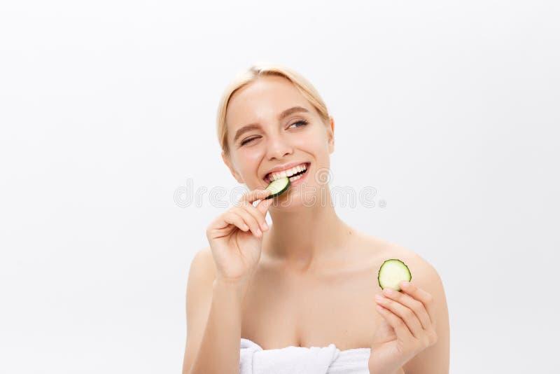 Сторона конца-вверх красивой женщины с чистой свежей здоровой кожей и с кусками огурца Изолировано на белизне стоковое изображение rf