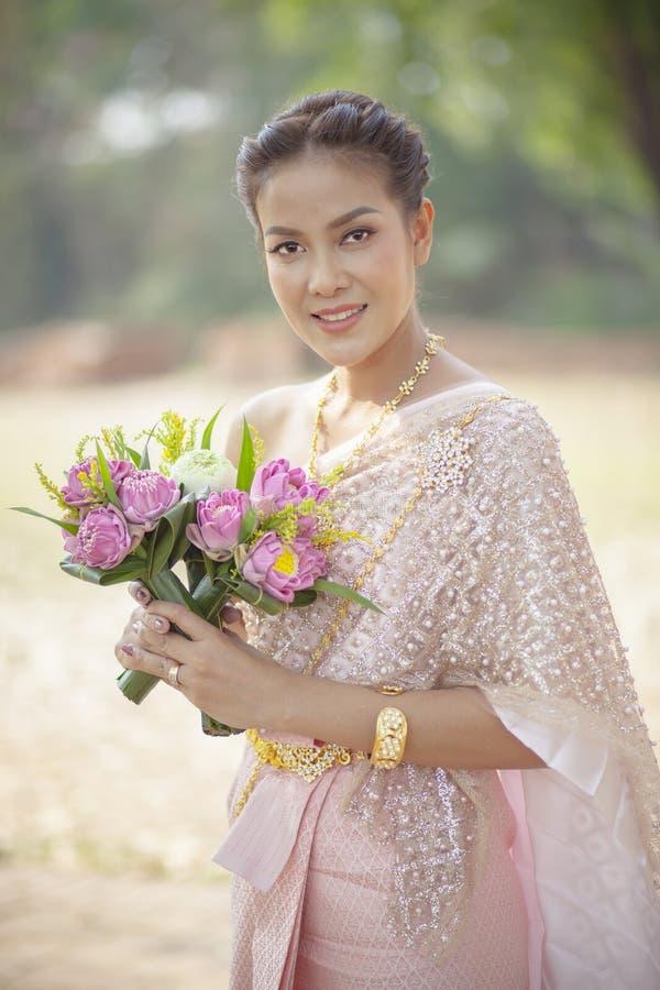 Сторона красивой азиатской женщины зубастая усмехаясь и розовый цветок лотоса стоковое фото rf