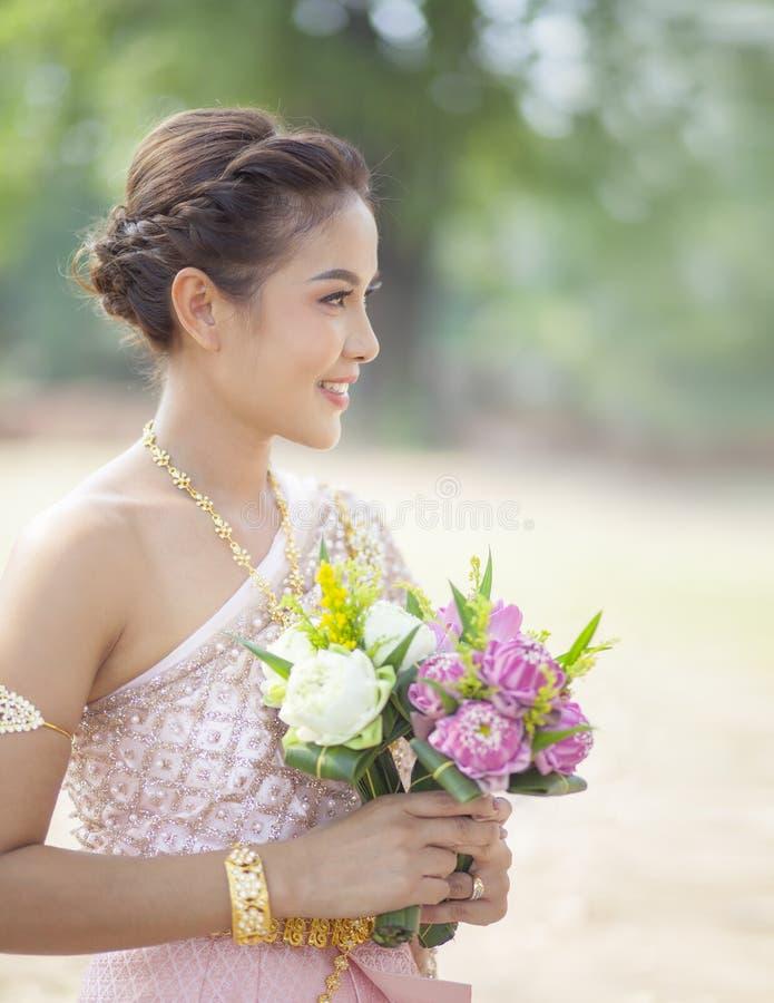 Сторона красивой азиатской женщины зубастая усмехаясь и розовый цветок лотоса стоковая фотография rf