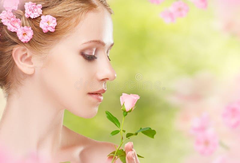 Сторона красоты молодой красивой женщины с розовыми цветками в ее ha стоковые изображения