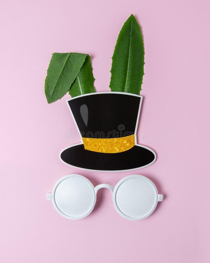 Сторона кролика сделанная из естественных зеленых листьев с белыми солнечными очками на пастельной розовой предпосылке Концепция  стоковые фотографии rf