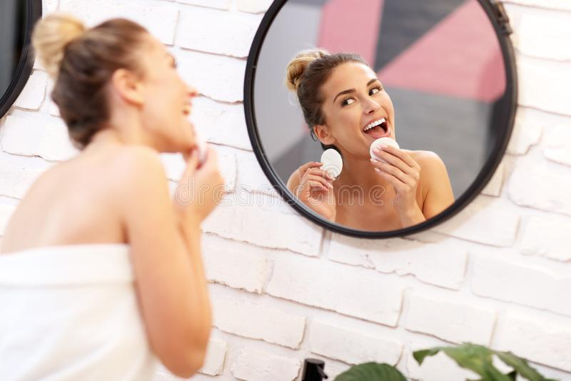 Сторона молодой женщины очищая в зеркале bathroom стоковые фотографии rf