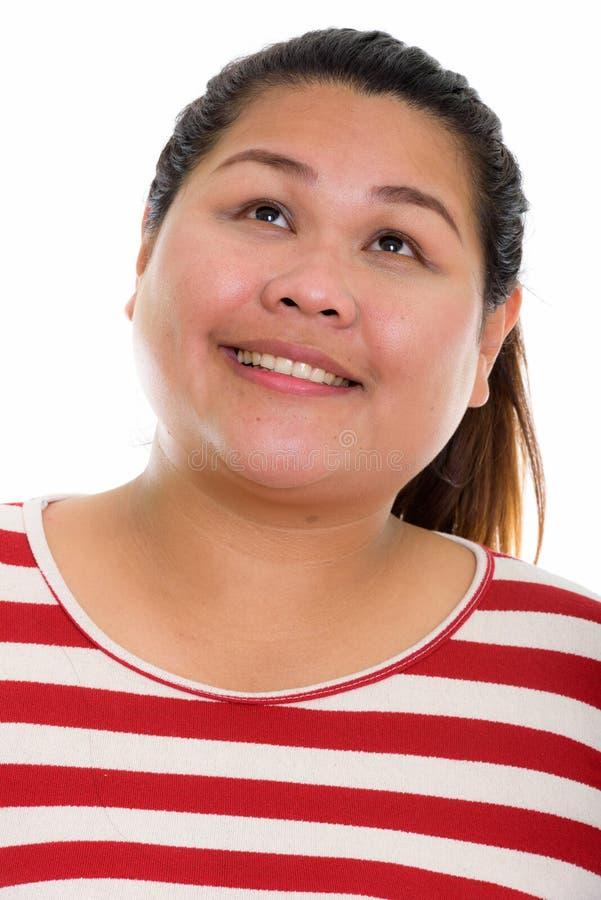 Сторона молодой счастливой жирной азиатской женщины усмехаясь пока мысль и l стоковые изображения