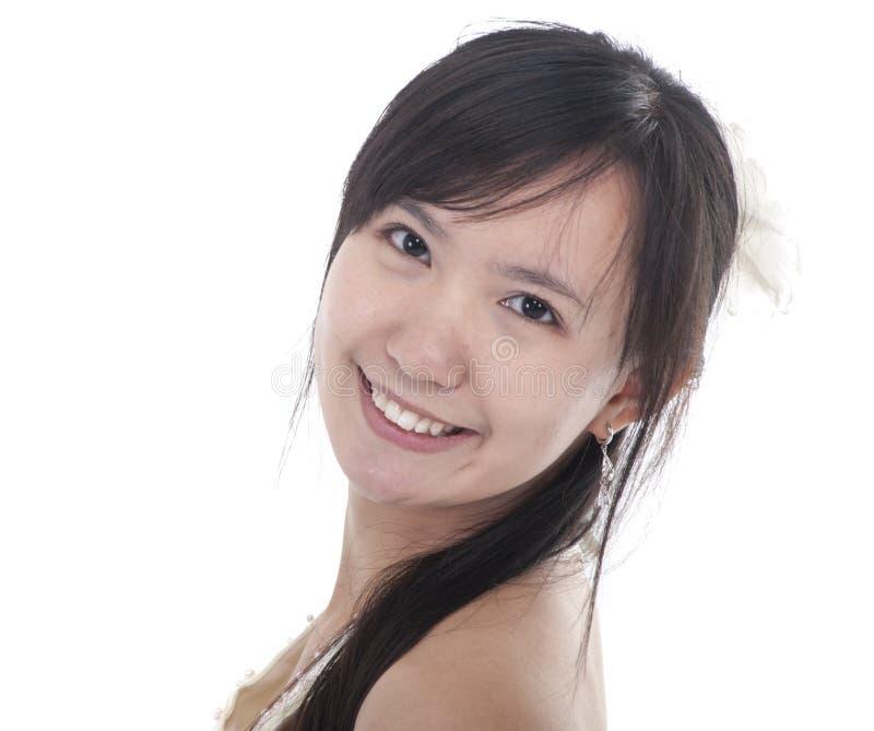 Сторона молодой азиатской женщины усмехаясь стоковые фото