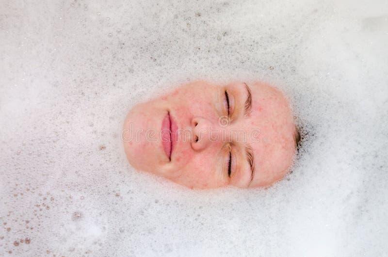Сторона молодой красивой девушки в белой ванне среди пузырей мыла от геля ванны пены, нагая с влажными волосами, наслаждается tre стоковые изображения rf