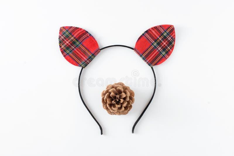 Сторона оленей рождества смешная сделанная красной изолированных шляпы ушей и меньшего coniferous конуса на белизне Концепция тор стоковые изображения