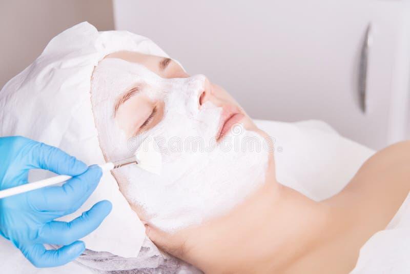 Сторона слезая маску, косметическую процедуру спа, skincare Женщина получая лицевую заботу beautician на салоне спа стоковое фото rf