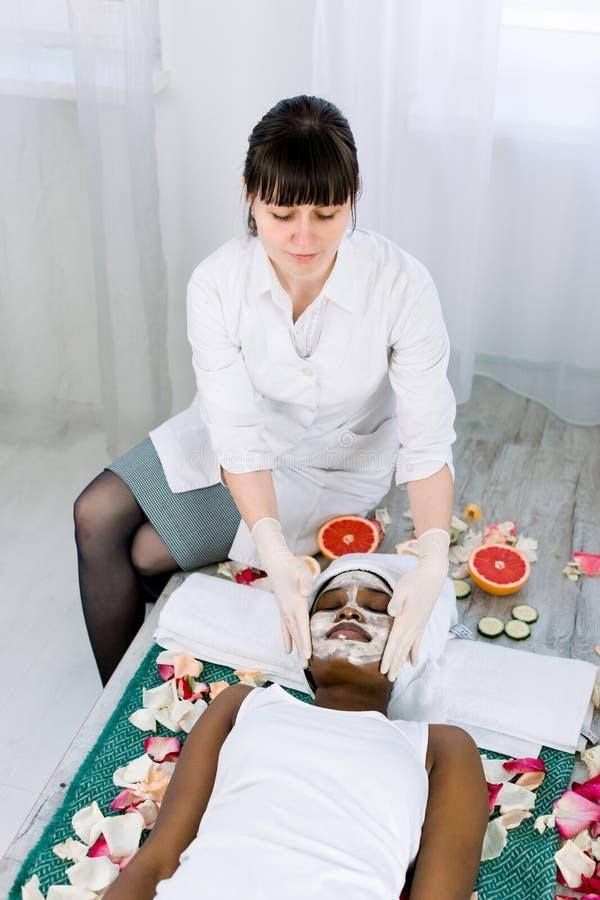Сторона слезая маску, косметическую процедуру спа, skincare Милая африканская женщина получая лицевую заботу beautician на салоне стоковое фото