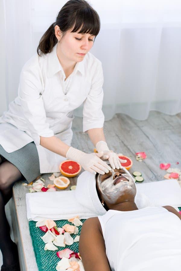 Сторона слезая маску, косметическую процедуру спа, skincare Милая африканская женщина получая лицевую заботу beautician на салоне стоковые фотографии rf