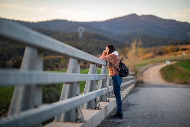 Сторона сняла красивой женщины полагаясь на загородке металла во время захода солнца стоковые изображения rf