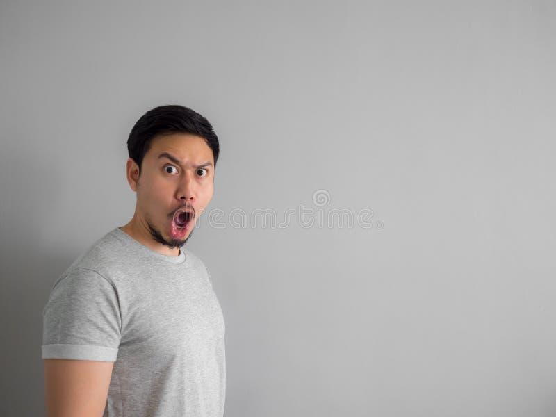 Сторона сотрясенная и вау человека с бородой в серой футболке стоковое фото