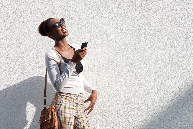 Сторона стильной молодой чернокожей женщины представляя с мобильным телефоном против белой стены стоковое изображение rf