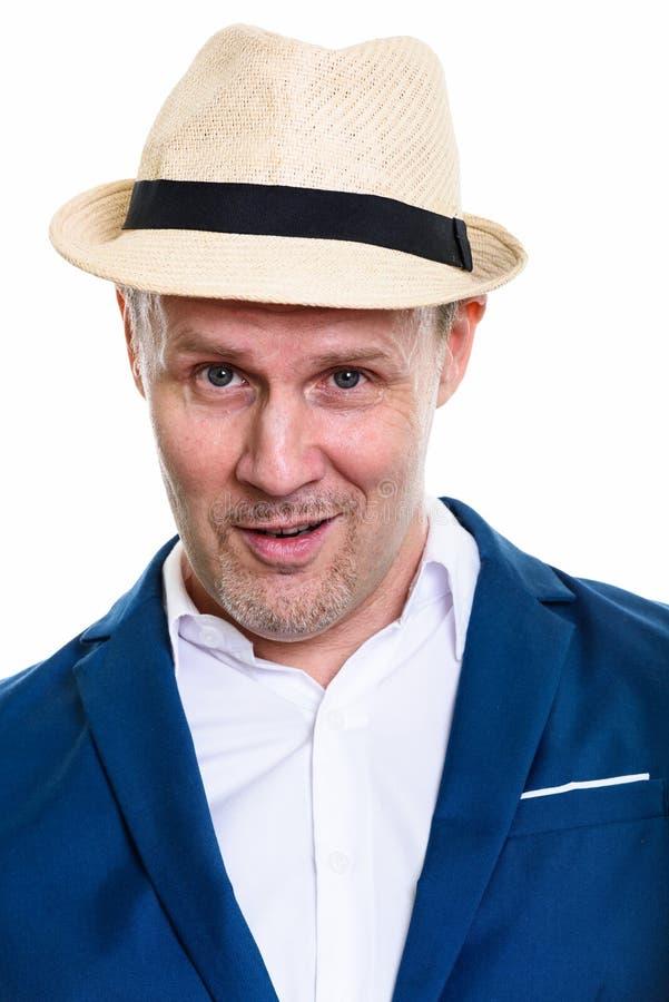 Сторона счастливого зрелого бизнесмена усмехаясь пока носящ шляпу стоковая фотография