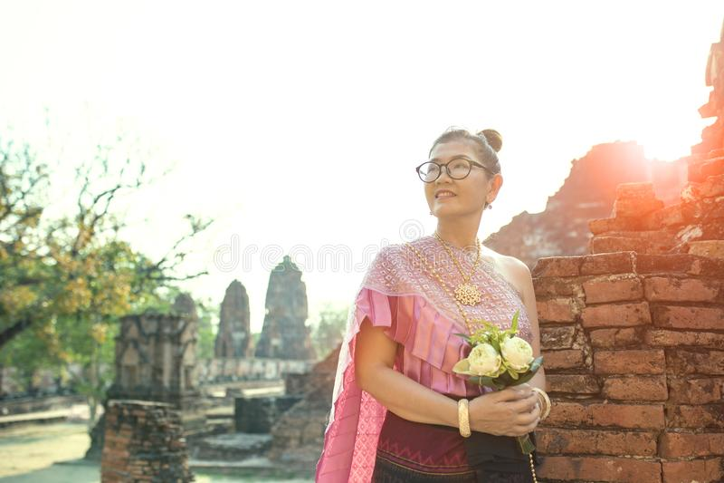 Сторона тайской женщины зубастая усмехаясь стоя с розовым цветком лотоса b стоковые изображения rf