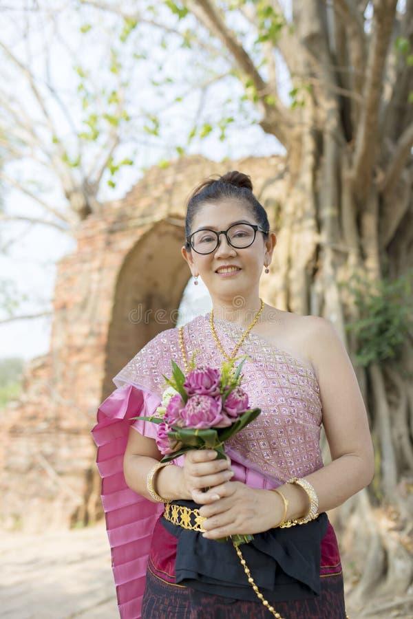 Сторона тайской женщины зубастая усмехаясь с розовым цветком лотоса в руке стоковые фотографии rf