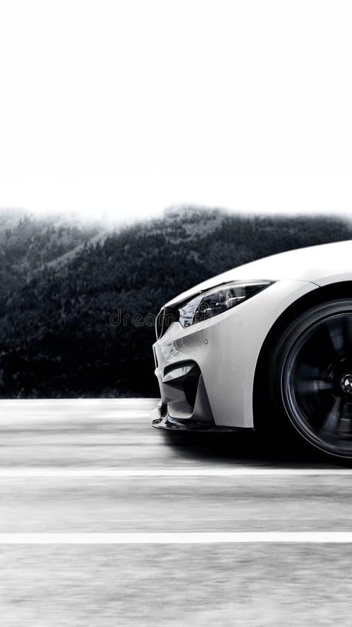 Сторона фронта быстрого белого автомобиля спорт на дороге стоковые фотографии rf