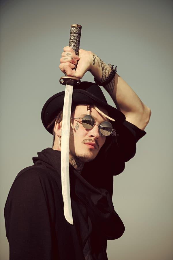 Сторона человека красивая Ратник в солнечных очках, черной шляпе и одеждах стоковое фото