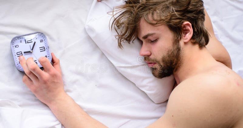 Сторона человека небритая сонная кладет взгляд сверху будильника подушки Oversleep проблема Сон Гая пропустил звенеть будильника стоковая фотография rf