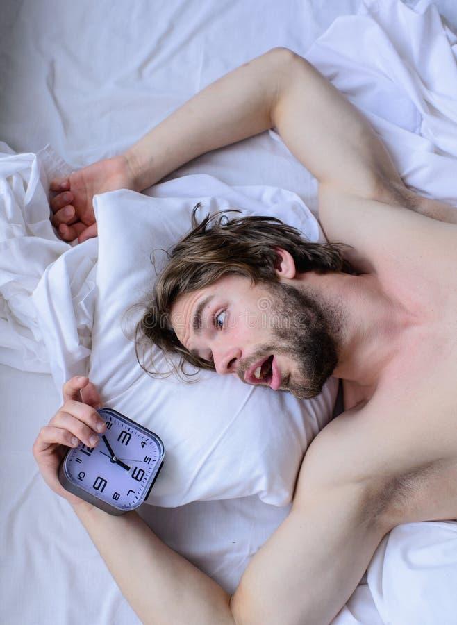 Сторона человека небритая удивленная сотрясенная положить взгляд сверху будильника подушки Гай пропустило звенеть будильника Полу стоковое изображение rf