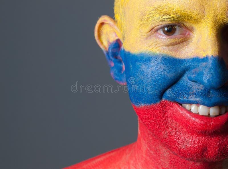 Сторона человека покрашенная с колумбийским флагом, усмехаясь выражением стоковые фотографии rf