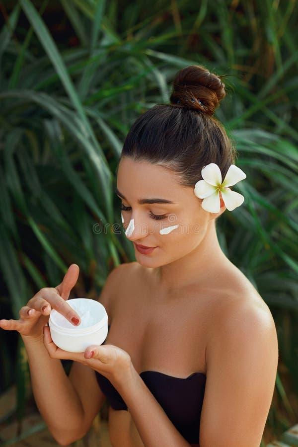 Сторона Skincare E Портрет женской держа moisturizing сливк в ее руке Молодая милая женщина прикладывая cosm стоковая фотография