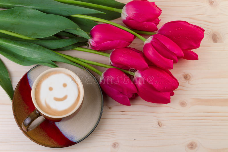 Сторона smiley кофе с красными тюльпанами на древесине Взгляд сверху стоковые изображения