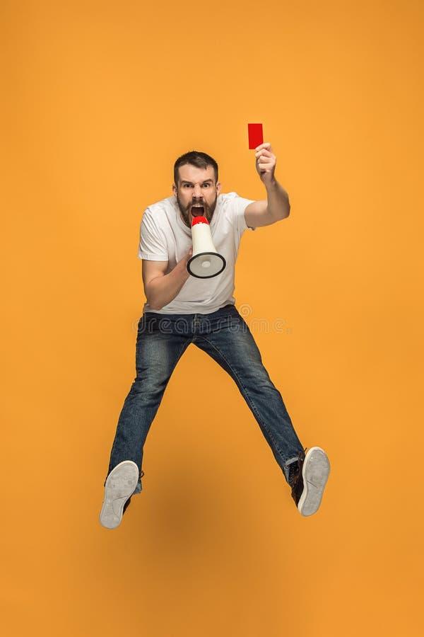 Сторонник футбола с красной карточкой на оранжевой предпосылке стоковое изображение rf