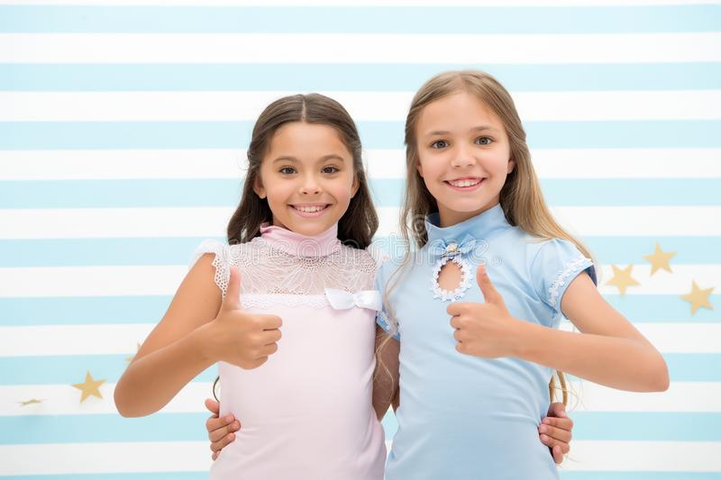 Стороны девушек усмехаясь счастливые обнимают один другого и большие пальцы руки выставки вверх показывать Объятия лучших другов  стоковые изображения rf