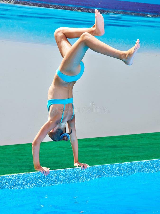 Стоят, что на его руках скачет спортсмен девушки в воду стоковое фото
