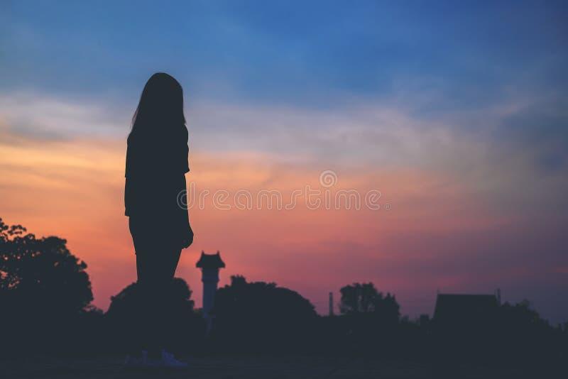 Стоящая женщина с небом перед предпосылкой захода солнца и космосом экземпляра стоковые изображения