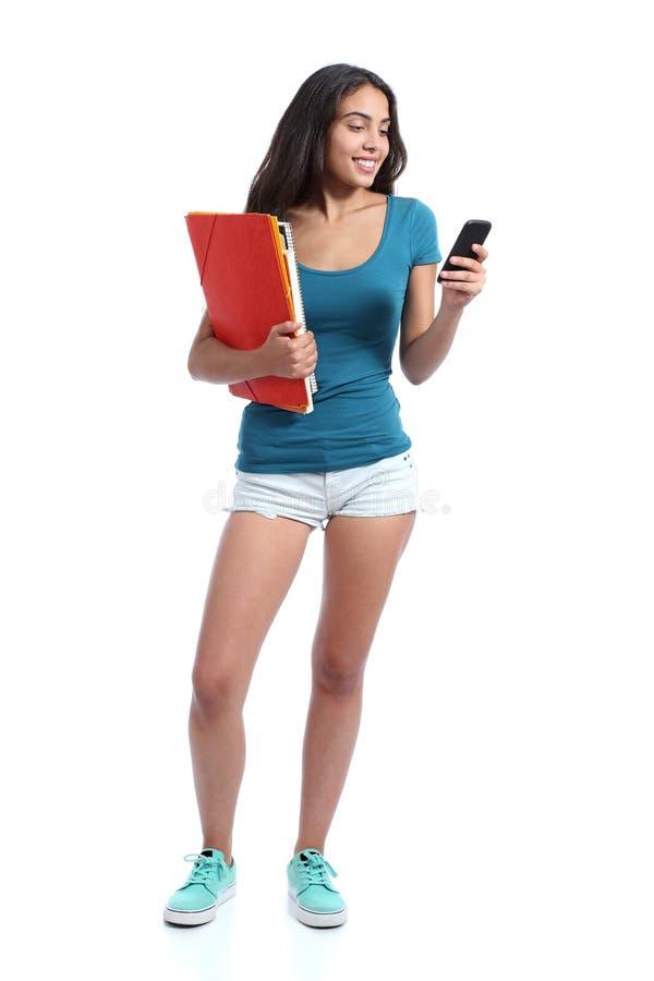 Стоящая предназначенная для подростков девушка держа папки и отправляя СМС в умном телефоне стоковое фото
