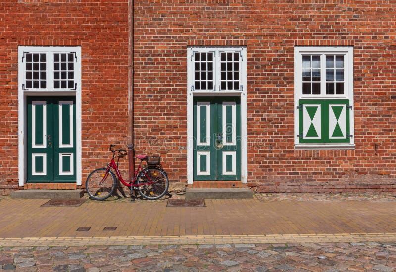 Стоящая склонность велосипеда против стены исторического дома в Потсдаме стоковое фото rf