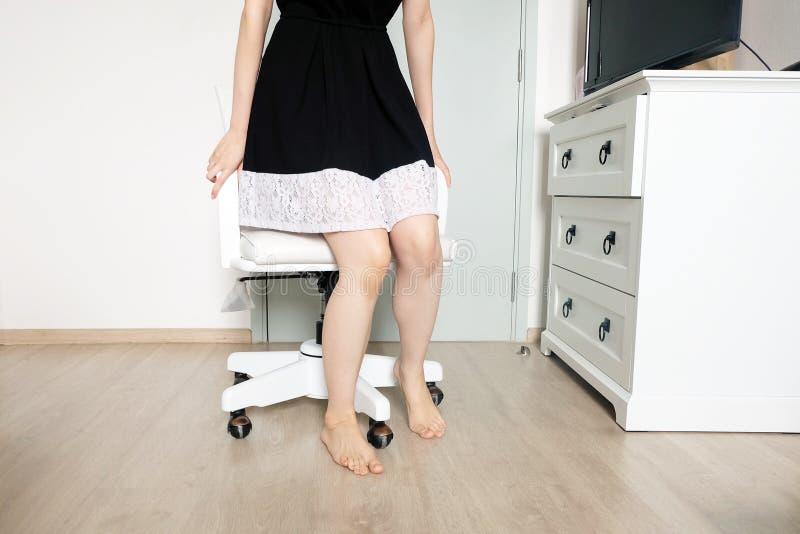 стоящие детеныши женщины Женщина в черном платье и розовом маникюре ногтей Ноги красивой женщины тонкие с Barefeet в белой комнат стоковая фотография rf