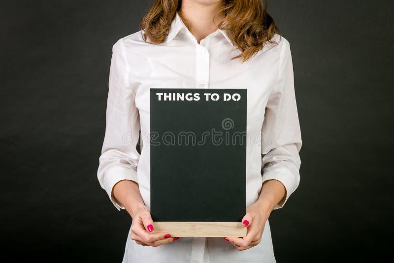 Стоя белокурая девушка в белой рубашке, с красным маникюром, с деревянным знаком в его руках Надпись на плите на bl стоковые фотографии rf