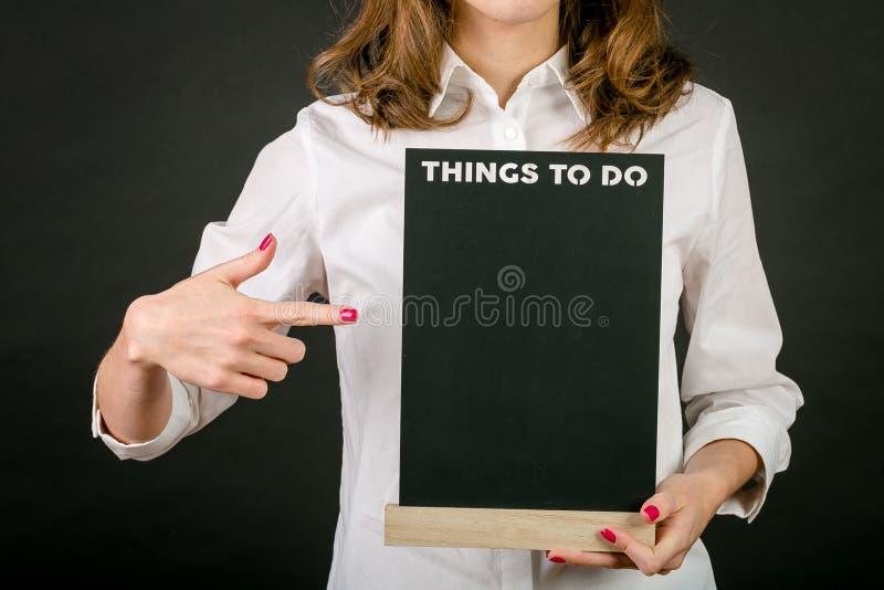 Стоя белокурая девушка в белой рубашке, с красным маникюром, с деревянным знаком в его руках Надпись на плите на bl стоковое изображение