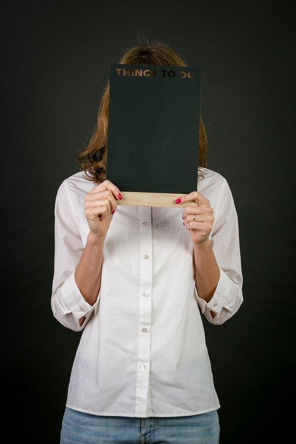 Стоя белокурая девушка в белой рубашке, с красным маникюром, с деревянным знаком в его руках Надпись на плите на bl стоковое изображение rf