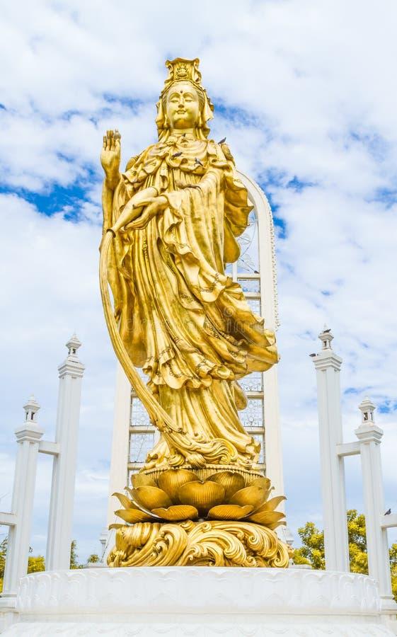 Стоя золотая статуя Guanyin держит вазу святой воды стоковая фотография