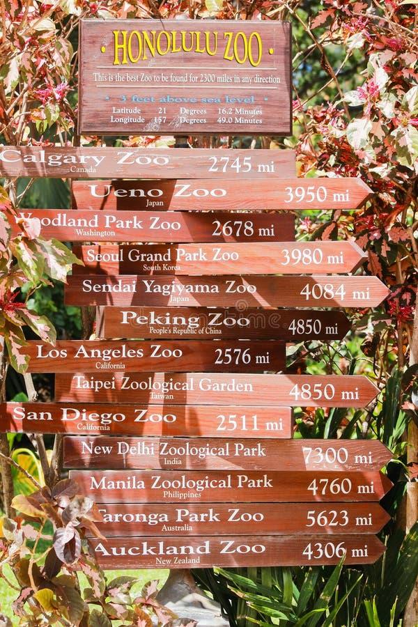 Столб знака на зоопарке Гонолулу давая расстояния в милях к другим международным зоопаркам стоковые фото
