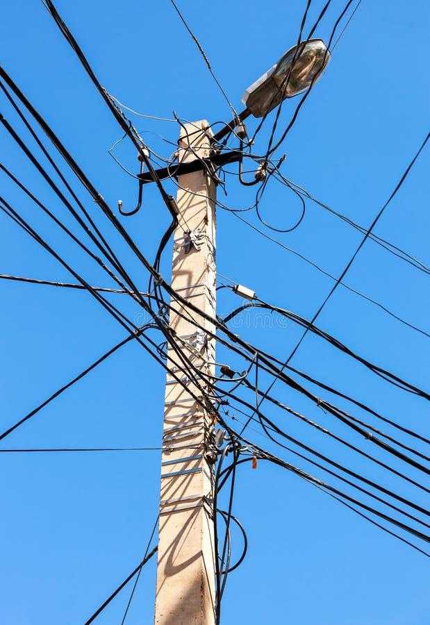 Столб электричества с проводом против голубого неба стоковое изображение