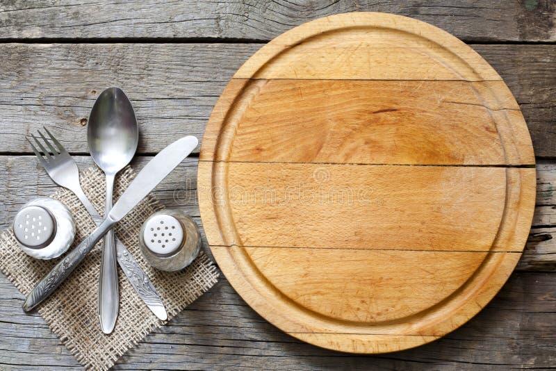Столовый прибор и винтажная пустая предпосылка еды разделочной доски стоковое изображение