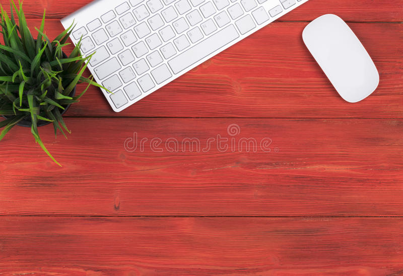 Стол офиса с космосом экземпляра Приборы беспроводная клавиатура и мышь цифров на красном деревянном столе, взгляд сверху стоковое изображение