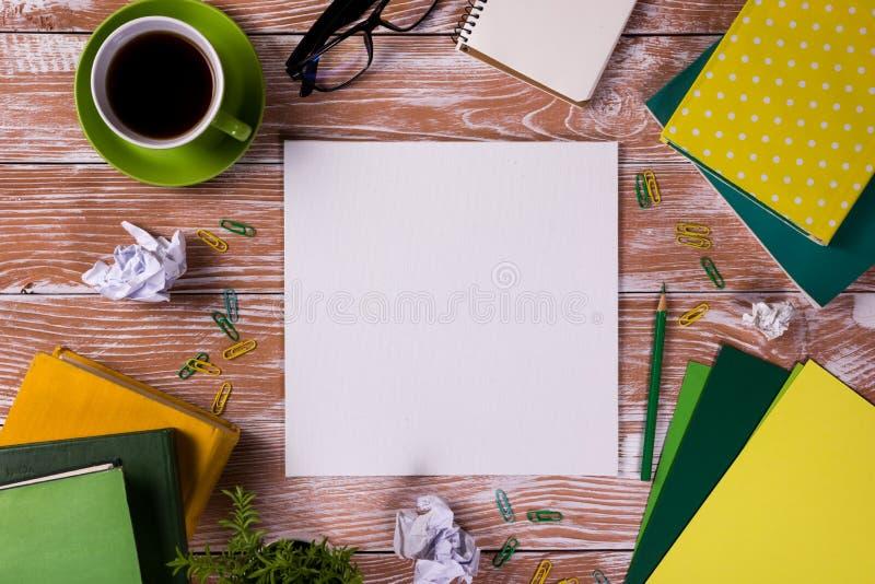 Стол с поставками, белый пустой блокнот таблицы офиса, чашка, ручка, ПК, скомкал бумагу, цветок на деревянной предпосылке top стоковое изображение