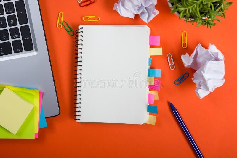 Стол таблицы офиса с комплектом красочных поставек, белым пустым блокнотом, чашкой, ручкой, ПК, скомкал бумагу, цветок на красном стоковые фото