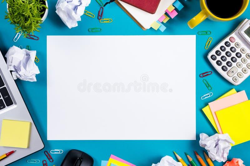 Стол таблицы офиса с комплектом красочных поставек, белым пустым блокнотом, чашкой, ручкой, ПК, скомкал бумагу, цветок на сини стоковая фотография rf