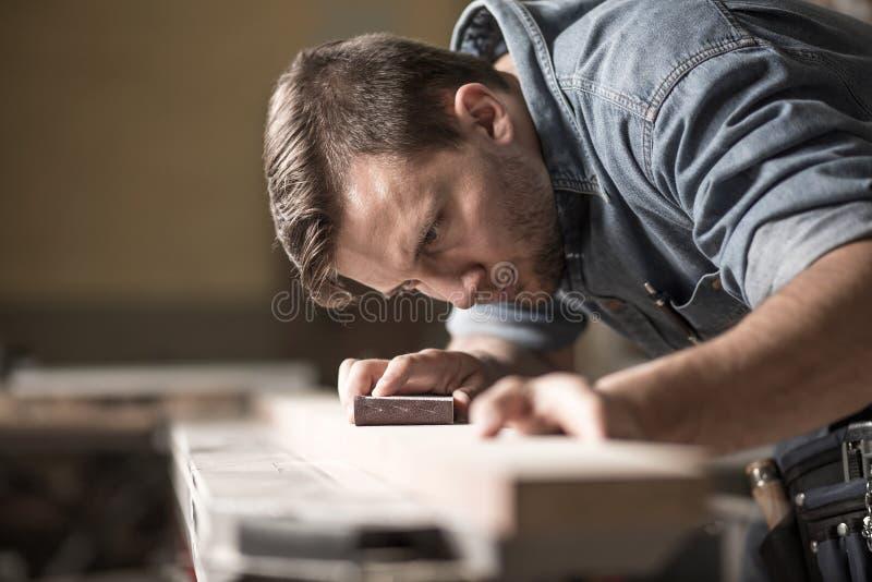 Столяр-краснодеревщик во время работы в мастерской стоковое фото
