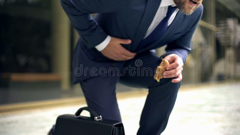 Страдание менеджера от неожиданной корчи живота, нездорового влияния питания, гнойника стоковое фото rf