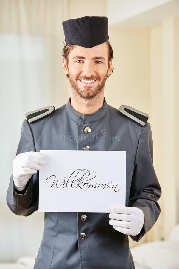 Страница гостиницы держа знак говоря Willkommen стоковое фото rf